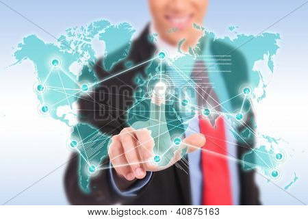 smiling business man making worldwide connections by pushing a button on a virtual screen