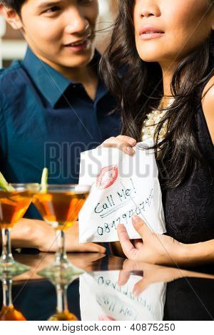 Asian woman seduces the man in restaurant and gives him her number on a napkin