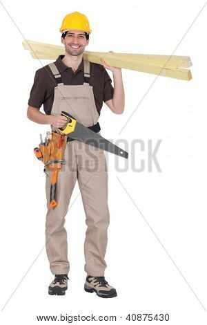 craftsman holding wooden boards and a saw