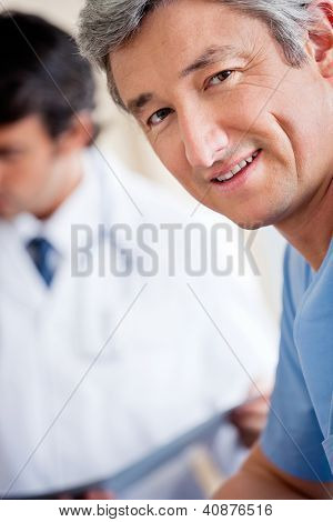 Portrait of mature male doctor smiling while colleague standing in background