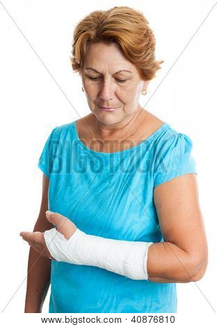 Senior hispanic woman with a broken arm on a plaster cast (isolated on white)