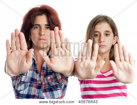 Young latin woman and a teenage girl signaling to stop with their hands extended isolated on white (useful to campaign against abuse,violence or discrimination)