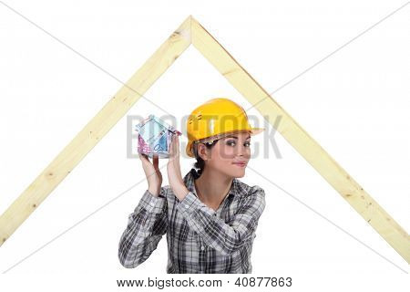 mischievous female joiner holding miniature house