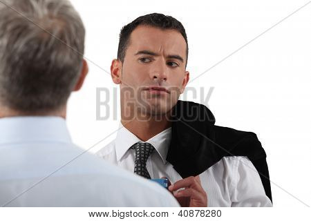 Man looking suspiciously at his colleague