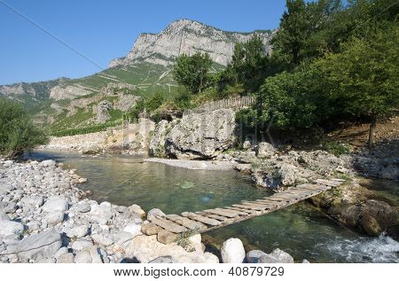small wooden bridge on a tributary creek of Cemi River in Commune Kelmend, Albania