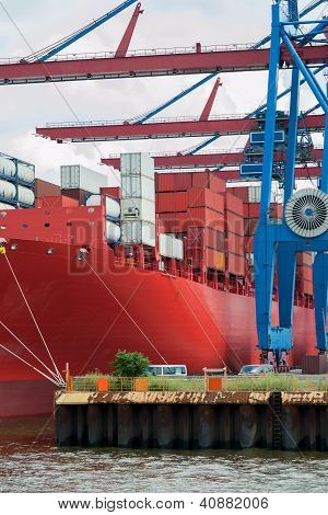 Large containership at port, ready for unloading.