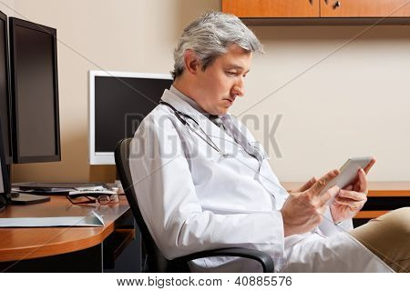 Serious mature male doctor looking at digital tablet while sitting by desk