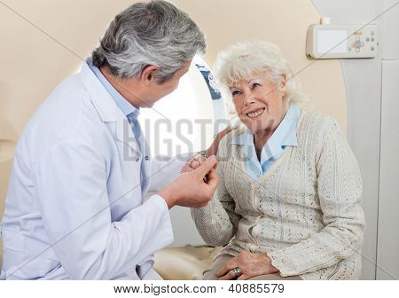 Mature male doctor comforting senior female patient before CT scan test