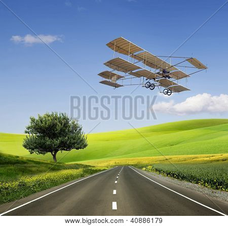 Green Grass Field Landscape with fantastic clouds in the background and old aircraft on the green field and road