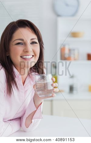Close-up portrait of young woman with glass of water in the kitchen