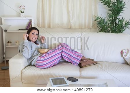 Young bored woman in nightwear sitting on couch and having popcorn at home