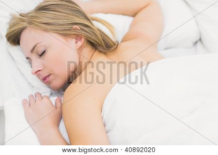 Close-up of pretty young woman sleeping in bed at home