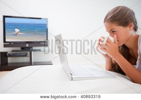 Young woman taking a sip of coffee while surfing the internet in the living room