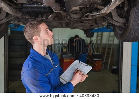 Male mechanic under car preparing checklist in workshop