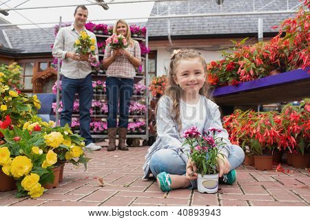 Family holding flower pots and smiling with little girl sitting on ground in garden center