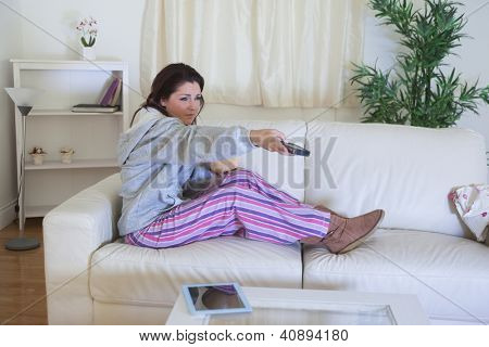 Young woman changing channels with remote control in living room at home