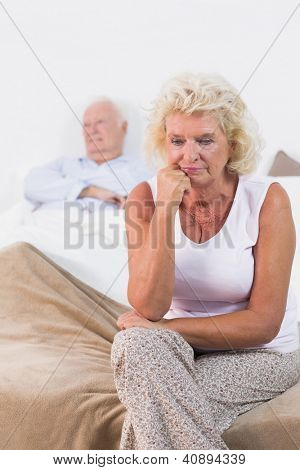 Discouraged old woman sitting on the bed with old man in background
