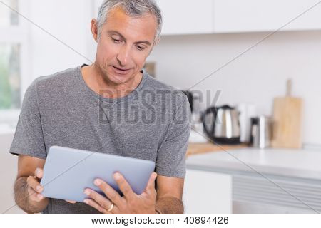 Mature man using his digital tablet in the kitchen
