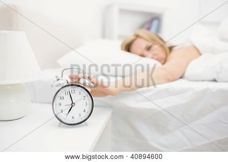 Irritated young woman in bed extending hand to alarm clock at home
