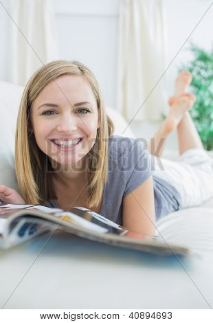 Portrait of casual young woman with magazine lying on couch at home