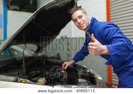 Retrato de gesticular mecánico pulgar hacia arriba, como comprueba el nivel de aceite del coche