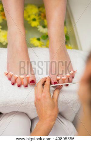 Close-up of woman polishing toe nails at spa center