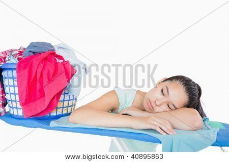 Mulher dormindo em uma tábua de passar perto de uma cesta cheia de roupa em um fundo branco