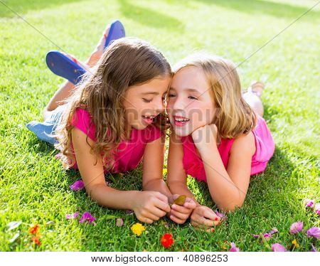 children friend girls playing whispering on flowers grass in vacations