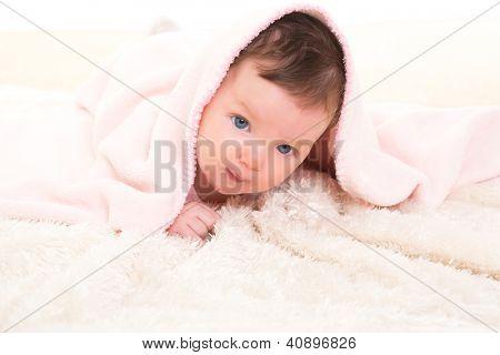 baby girl under hidden pink blanket on winter white fur background