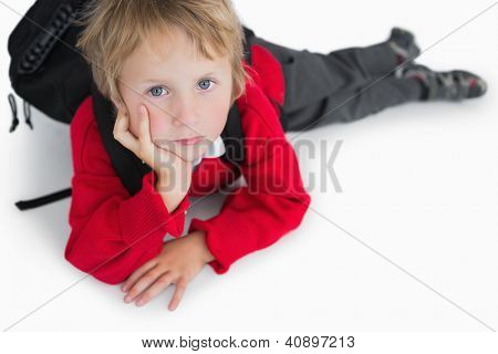 Portrait of young boy lying on floor with schoolbag