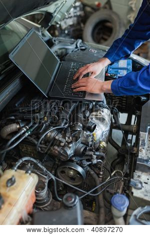 Close-up of male car mechanic using laptop on car engine