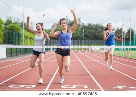 Female athletes celebrating as they cross finish line on track field