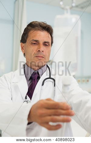 Thoughtful doctor standing in the hospital adjusting IV