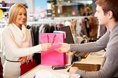 stock photo of department store  - Portrait of pretty woman giving credit card to shop assistant while paying for her purchase - JPG