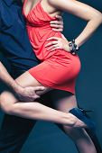 stock photo of flirtatious  - Vertical shot of a dancing couple captured in a dynamic motion - JPG