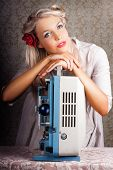 foto of starlet  - Beautiful Glamorous Young Blonde Starlet Leaning On Top Of An Old Reel To Reel Cine Projector Looking Up With A Dreamy Faraway Look Recalling Her Stardom - JPG
