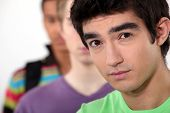 image of cynicism  - Young man standing beside his friends - JPG