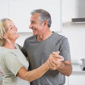 Smiling mature couple dancing together in the kitchen