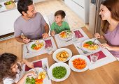 stock photo of father time  - Family smiling around a healthy meal in kitchen - JPG