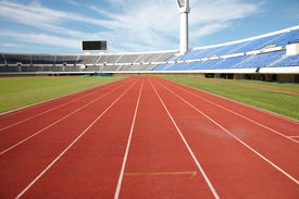 stock photo of track field  - stadium track and field area empty on a sunny day - JPG