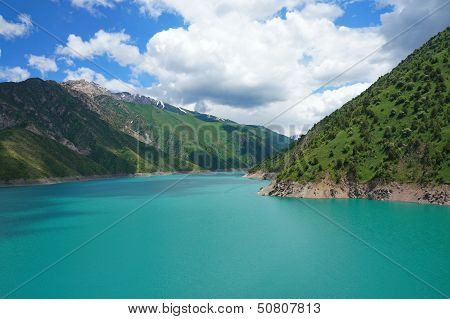 Fascinating lake with high coast and blue sky with amazing clouds