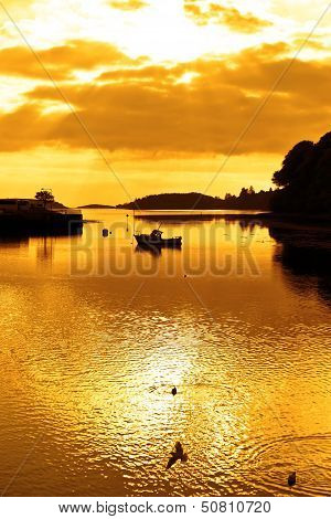 Bright Orange Silhouette Of Boat And Birds At Sunset