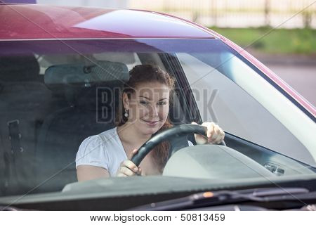 Smiling Woman Holding Steering Wheel And Looking Through The Windscreen