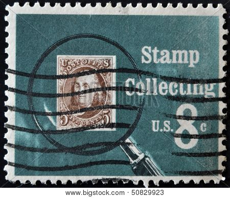 A stamp printed in USA shows Pictures magnifying glass over United States postage stamp