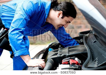 Mechanic Checking Under The Car Engine