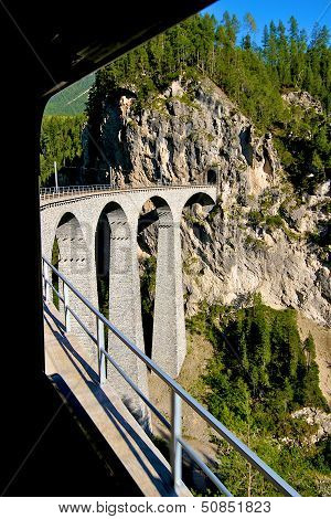 Bernina Express, Swiss Red Train Passing Over A Viaduct High In The Alps In Switzerland. Bernina Lin