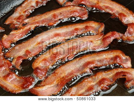 Bacon rashers being cooked in frying pan.