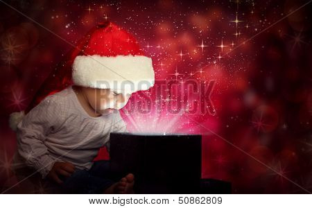 Happy Baby Child Girl In Christmas Hat Opening A Magic Gift Box