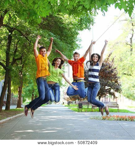 Happy group of young people jumping in park