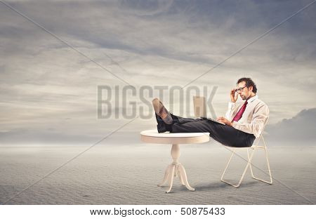 businessman working with tablet comfortable sitting with feet on the table in the desert